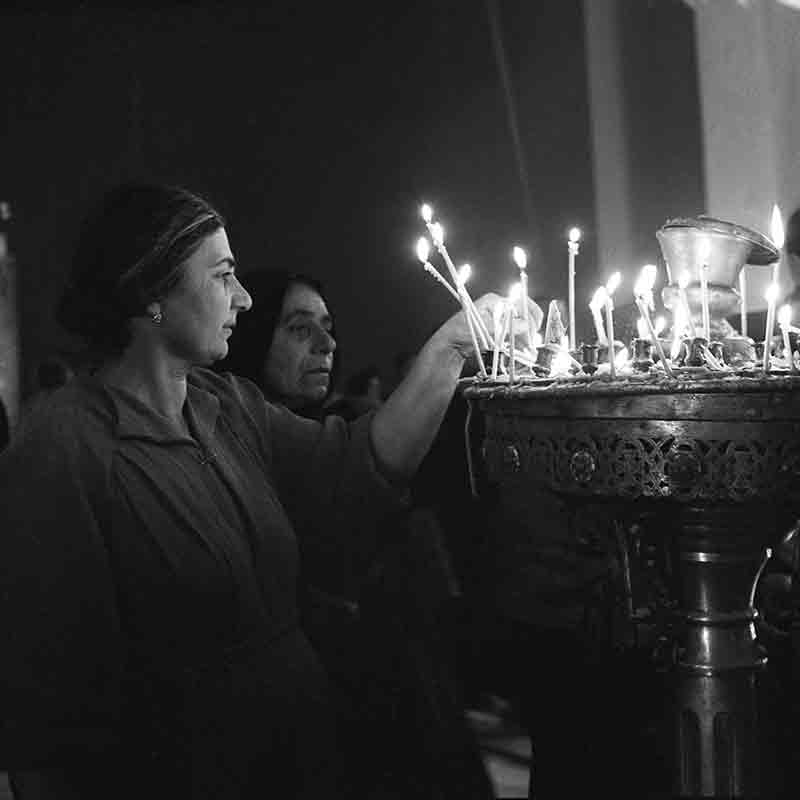 People in Armenian church light candles