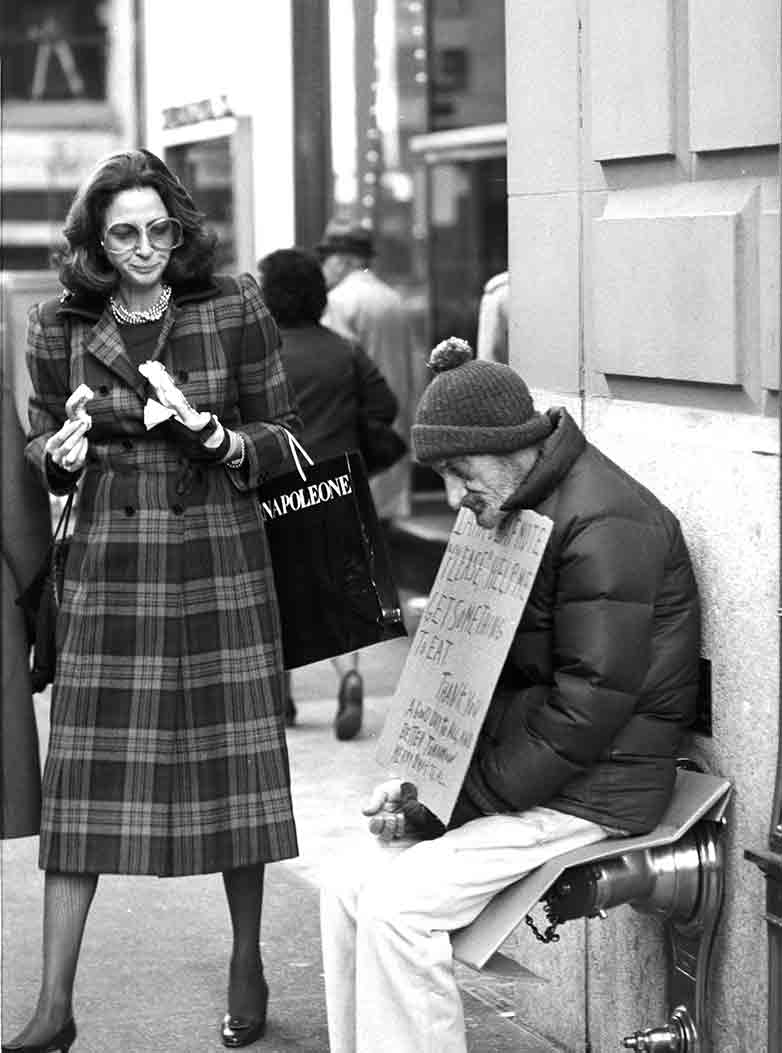 Rich woman in fur and beggar on the street in Manhattan