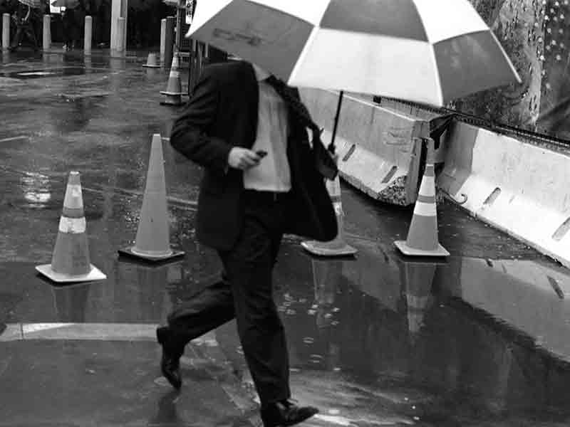 Man with umbrella running
